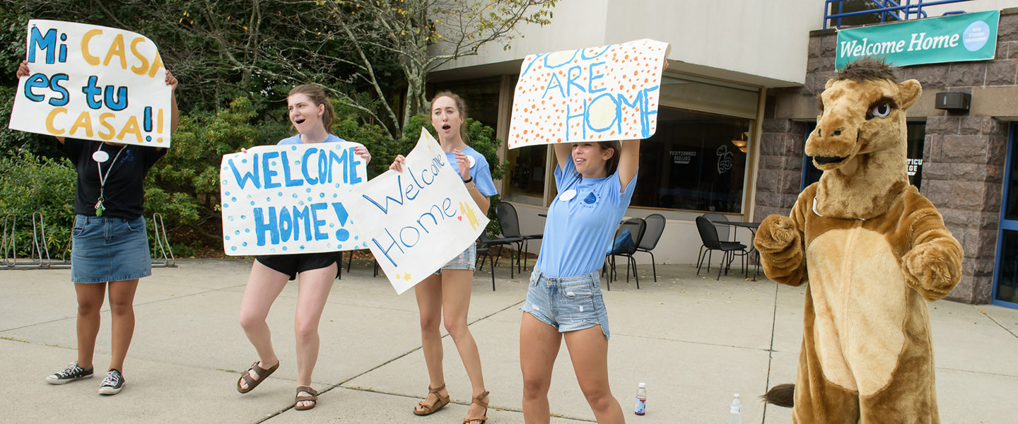 Student leaders welcome new students with signs and cheers.