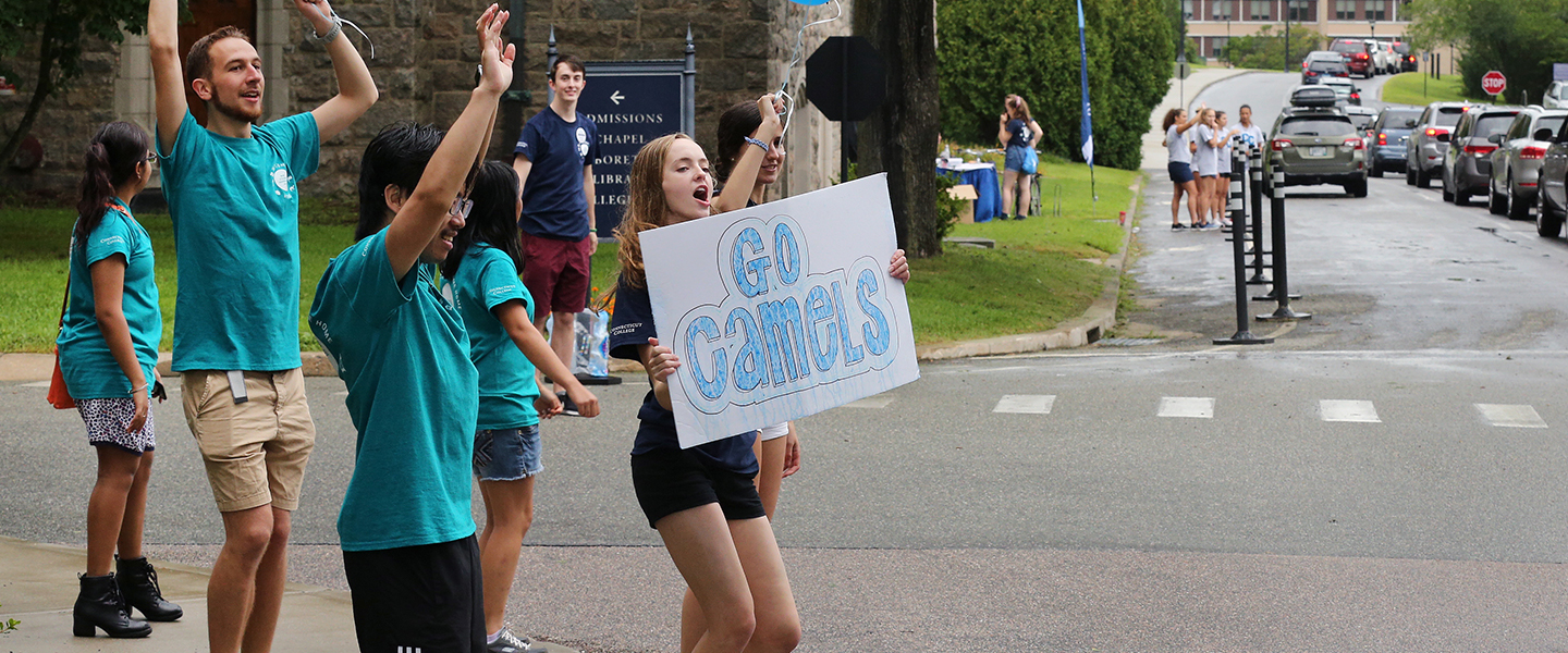 Upperclass students welcome first-years to campus with inviting signs at the college entrance.