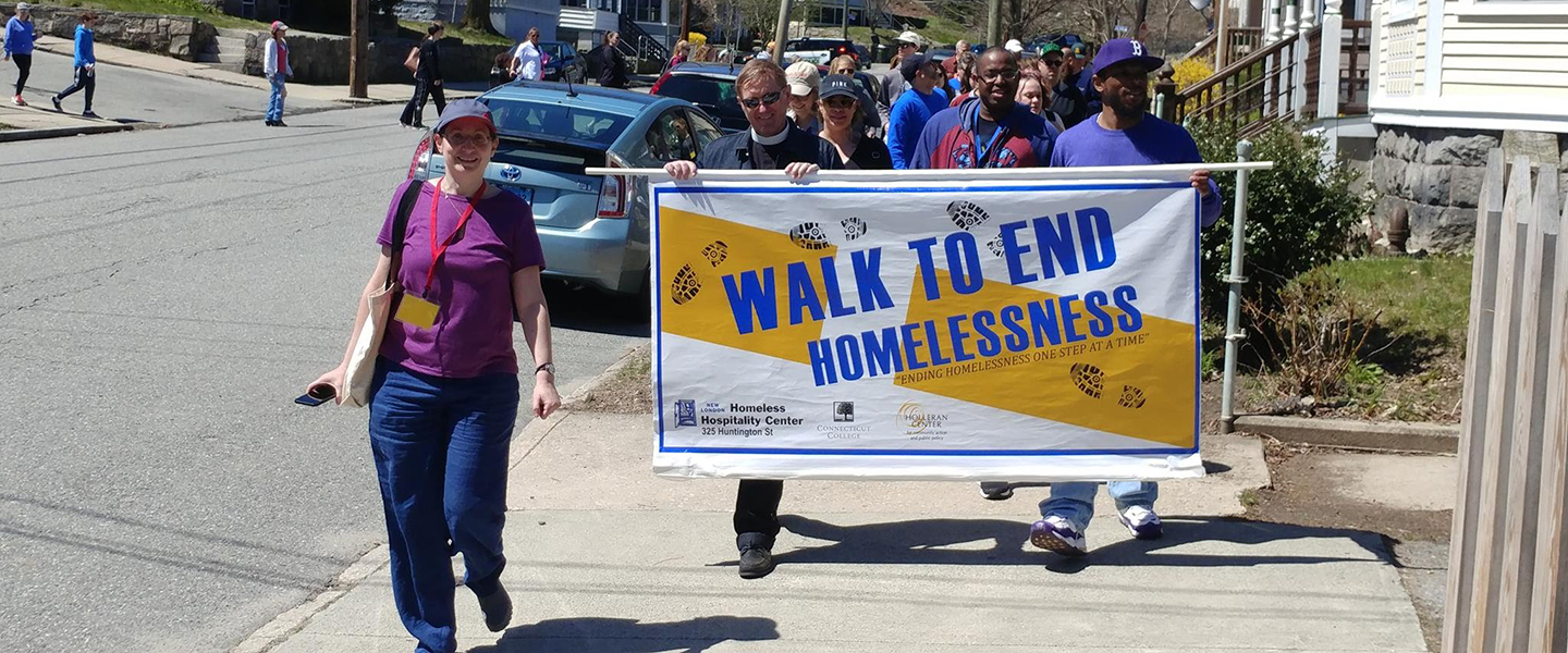 Walkers parade through New London holding the Walk to End Homelessness sign.