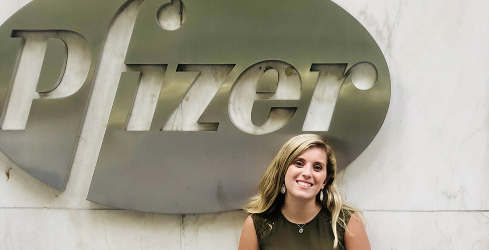 Victoria Azoulay in front of the Pfizer logo.