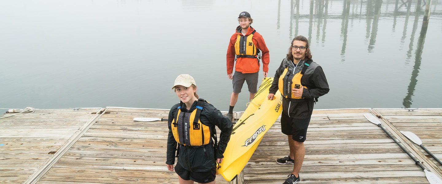 Students carrying yellow kayak