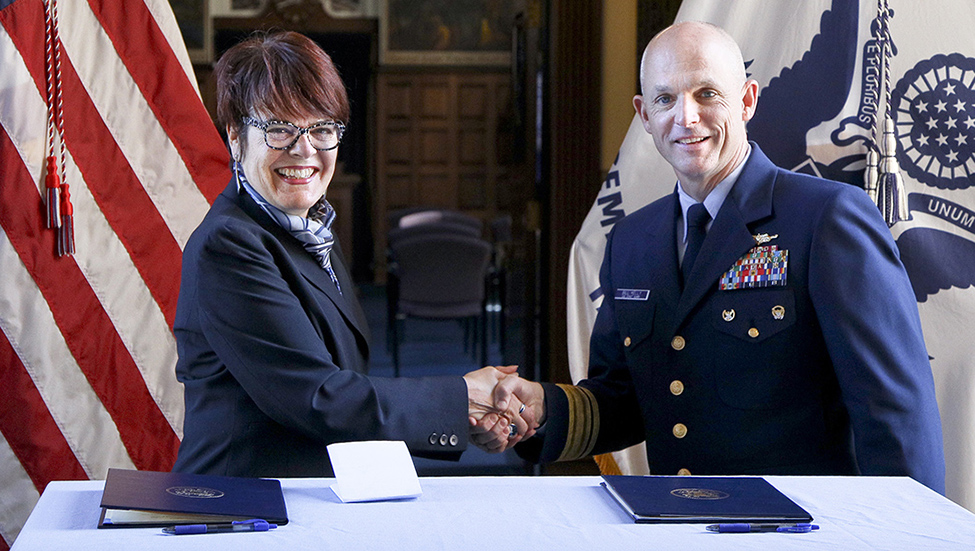 Connecticut College President Katherine Bergeron, left, and the superintendent of the U.S. Coast Guard Academy, Rear Admiral William G. Kelly, shake hands after signing the new Memorandum of Agreement.